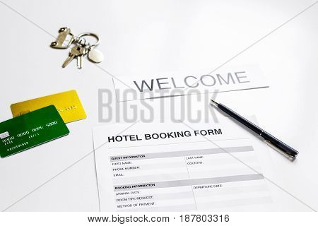 booking hotel room application form and keys on white desk background