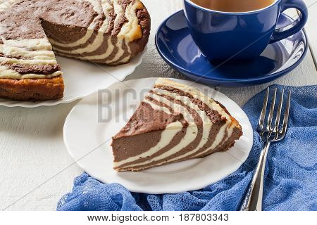 Delicious homemade chocolate cake with cottage cheese Zebra (Marble cake). Tasty breakfast. Piece of cake on blue plate blue cup and blue gauze textiles on white wooden table. Selective focus