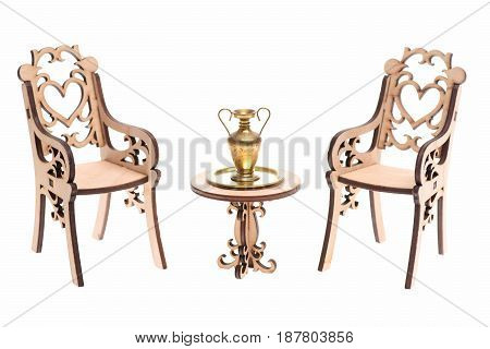 Golden Amphora On Tray On Wooden Table With Decorative Chairs
