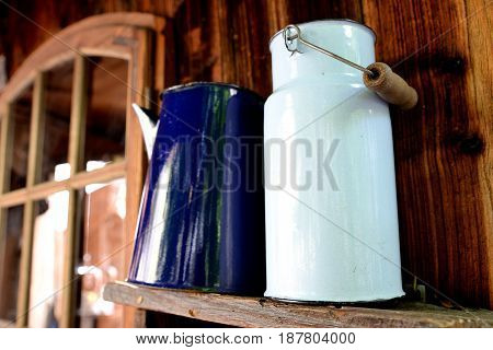 Old white milk bubble standing on a wooden shelf and blue jug