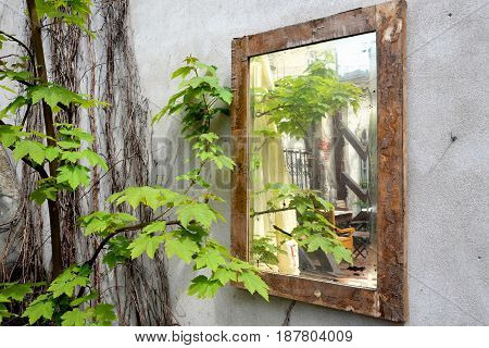 Old mirror hanging in Cracow on the wall of a brick walled house