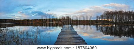 Panorama Landscape. Wooden Pier On The Lake At Sunset, Clouds Reflection In The Water.