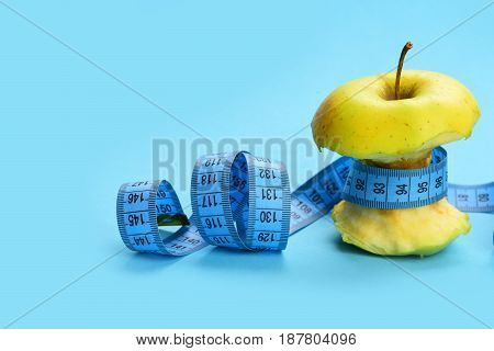 Apple belted with blue curled measuring tape as a symbol of dietary nutrition isolated on light blue background copy space