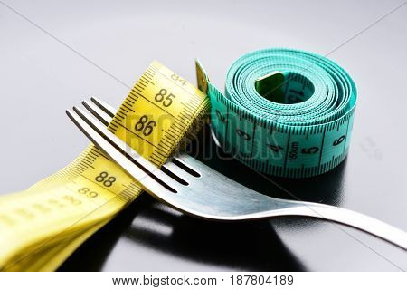 Roll Of Green Measuring Tape Next To Metal Fork