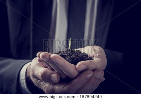 Retro vintage style image of a businessman holding a plant growing in rich soil cupped in his hands in a close up view conceptual image.