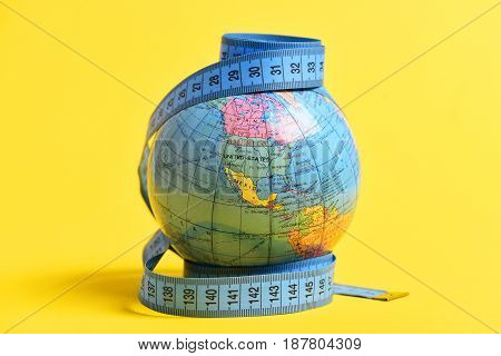 Globe and blue measuring tape isolated on bright yellow background. Concept of worldwide population and supply issue
