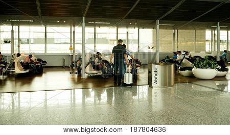 FRANKFURT GERMANY - JUL 3 2015: Interior of Frankfurt International airport with couple walking toward lounge area walking with trolley luggage delayed flight or plane arrival departure