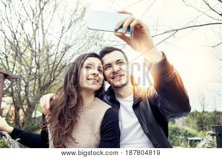 Nice Couple Boyfriends Takes A Selfie Relaxing In The Park Outdoor
