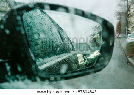 View throu car window at rear view mirror on a snowy day - senn by the driver point ov view personal perspective through wet windshield window
