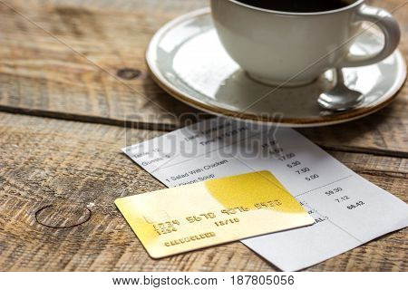 restaurant bill paying by credit card for cup of coffee on wooden table background