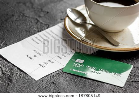 restaurant bill, credit card and coffee on dark table background