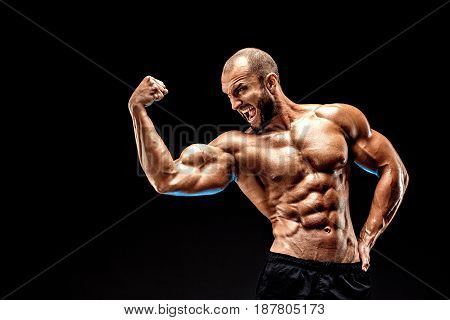 Strong bodybuilder man with perfect abs, shoulders, biceps, triceps and chest showing his biceps. Scream motivation.
