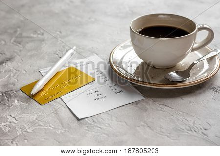 restaurant bill, credit card and coffee on stone table background