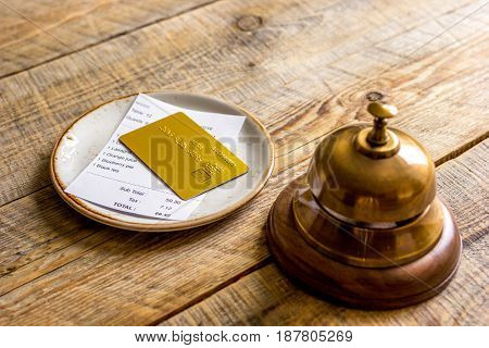 restaurant bill paying by credit card and waiter ring on wooden table background