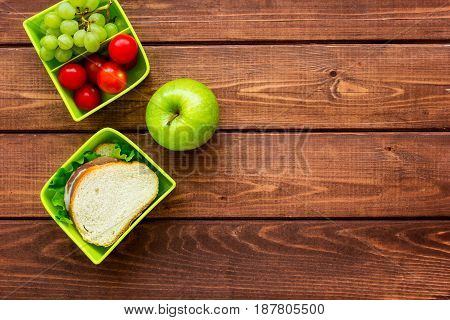 healthy break with apple, grape and sandwich in green lunchbox on home wooden table background flat lay mock-up