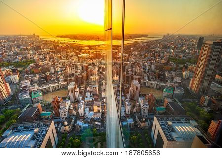 Aerial view of Osaka City central business downtown and Yodo River with its bridges at sunset. Osaka Skyline from Floating Garden Observatory Umeda Sky Building, Japan, reflect in the glass.