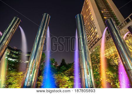 Scenic and colorful fountains at Umeda Sky Building, landmark and popular attraction in Umeda district, Osaka, Japan, at night.