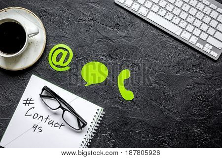 customer support service desktop with contact us signs and keyboard on dark office background top view mock-up