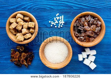 lumps of sugar in bowls on blue kitchen table background top view