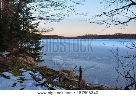 Calm Evening On The Frozen Lake Shore. Dawn Light In The Sky. Early Spring Nature Landscape