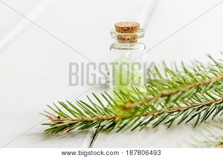 Bottles of natural sea salt and fir branches for aromatherapy and spa on white table background