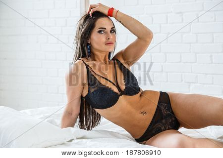Beautiful brunette girl sexy fitness in lingerie posing in the room interior, bright bedroom
