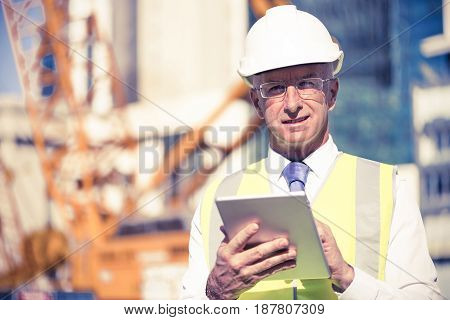 Senior engineer man in suit and helmet working on tablet pc