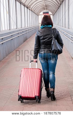 Woman In Jeans With A Red Suitcase