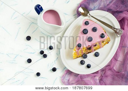Delicious homemade pie with cottage cheese cornflakes and blueberries. The cake is cut into pieces served with berry-yoghurt sauce. Tasty breakfast