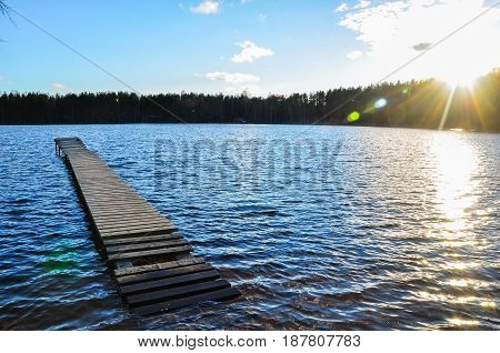 Flooded Wooden Bridge In The Blue, Waving Lake Water And Shining Sun.