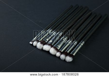 Professional makeup brushes on a black background, natural cloth