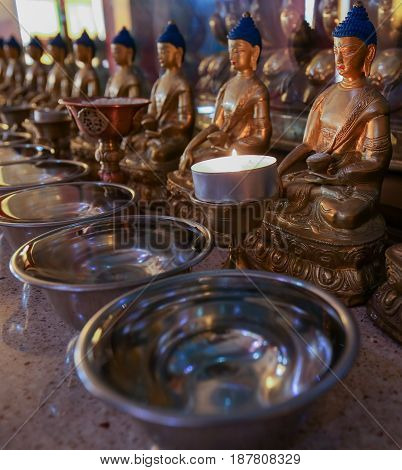 Figures of the sitting Buddha in front of the candle in the temple, Russia Elista