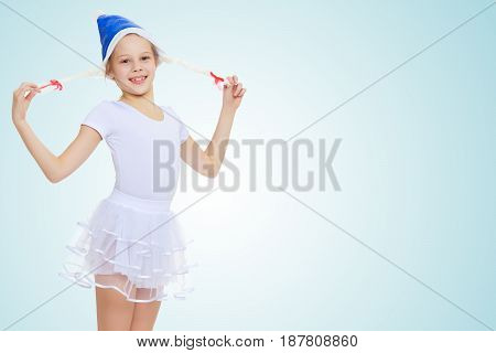 Cheerful little girl gymnast in white sport dress in a cap of Santa Claus.On the pale blue background.