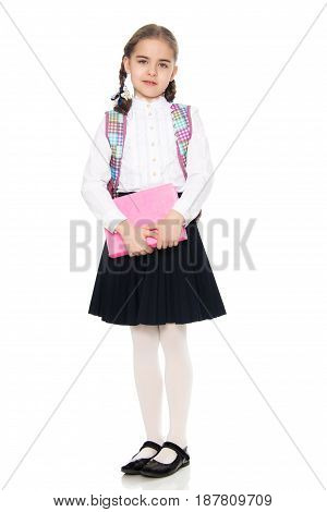 Beautiful little blond schoolgirl, with long neatly braided pigtails. In a white blouse and a long dark skirt.She holds the book in her hands.Isolated on white background.