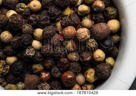 Overhead close up (macro) of a variety of mixed peppercorns filling a white ceramic bowl.