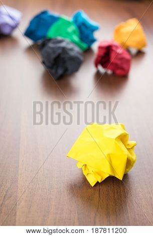 Yellow Crumpled Paper Ball On Dark Brown Wood Table With Group Of Colorful Crumpled Paper Ball At Ba