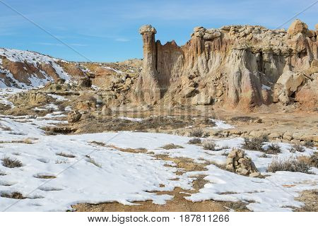 Towering rock formations stand against a bright blue sky, set in the lightly snow covered, dry arid landscape of the Wyoming Badlands