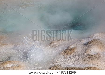 Bubbling hot water erupting in a crystal clear, aqua blue hot spring pool, with hot steam rising and silica edges