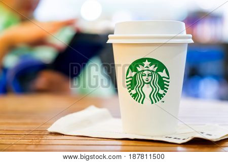 Bangkok Thailand-March 6 : Starbucks Hot beverage coffee on table with woman used mobile at background on 6 March 2016 at department store Bangkok Thailand..