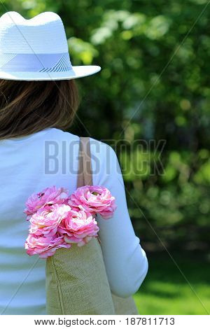 Female in white summer fashion carries pink flowers in shoulder bag.