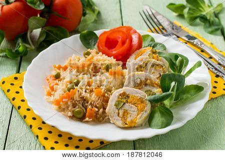 Stuffed chicken breast roll with carrots and green peas. Sliced pieces. Served with spicy rice and vegetables. Green wooden background. Selective focus