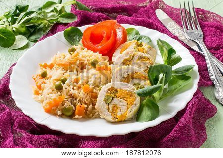 Stuffed chicken breast roll with carrots and green peas. Sliced pieces. Served with spicy rice and vegetables. Green wooden background burgundy gauze textile. Selective focus