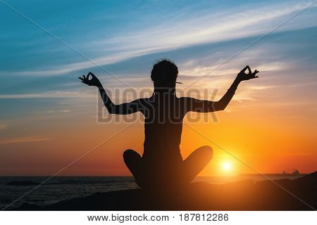 Silhouette of young yoga woman does meditation on sea beach at amazing sunset.