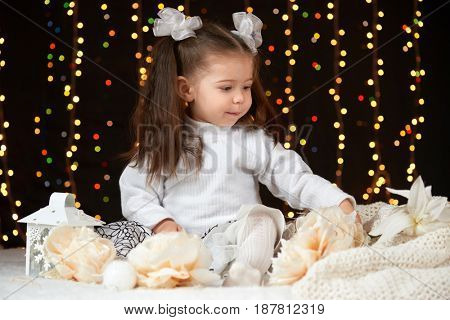 child girl portrait in christmas decoration, happy emotions, winter holiday concept, dark background with illumination and boke lights