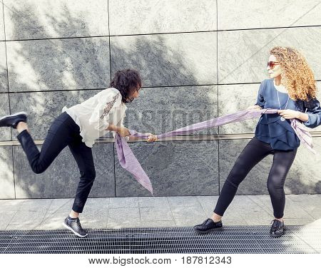 Two Pretty Girls Improvise A Tug Of War With A Scarf
