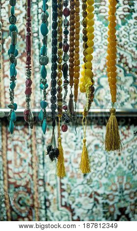 Variety of Islamic prayer beads displyed in a shop. Close up of hanging rosary.