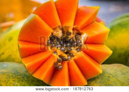 Closeup of bright orange papaya cut artfully with brown seeds surrounded by light green skinned whole papayas in the background