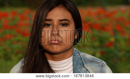 Sad Face Of Hispanic Teenager Sitting in Flower Meadow