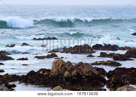 Waves crashing onto a rocky tide pools during high tide taken at the California Coast on a cloudy day