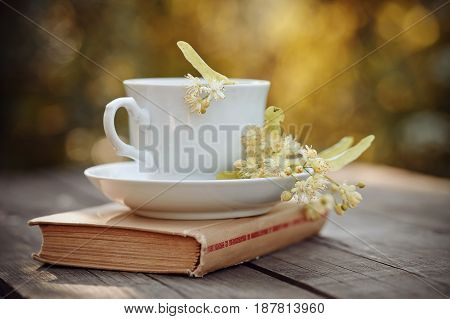 Lime tea in a white mug and the book on a wooden table.